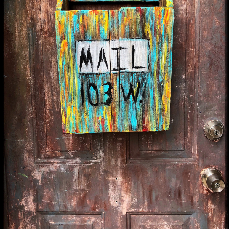 Handpainted artistic mailbox hanging on an old wooden door.